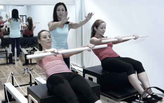 Roll downs on the long box on the Pilates Reformer at Peacock Pilates London - Work those stomach muscles.